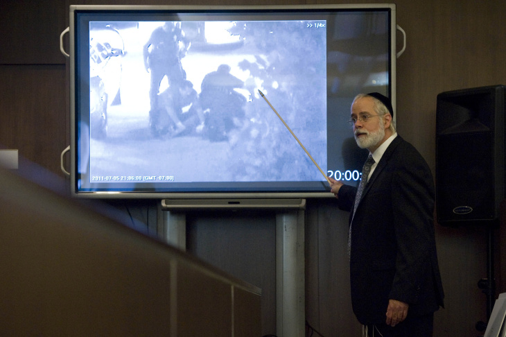 Defense attorney Michael D. Schwartz, who is representing former Fullerton police officer Jay Cicinelli in the case of the death of Kelly Thomas, reviews video footage of the incident with the jury during his closing argument Wednesday.