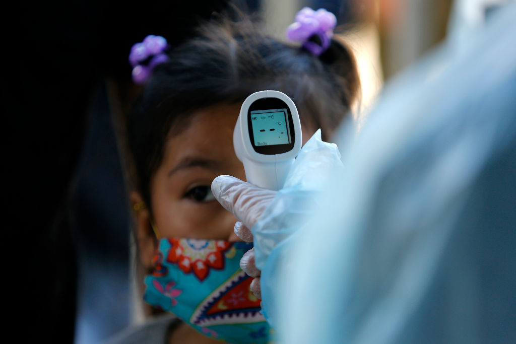 The temperature of a Bolivian child is measured in front of Bolivian embassy during a demonstration requesting repatriation on April 28, 2020 in Santiago, Chile.