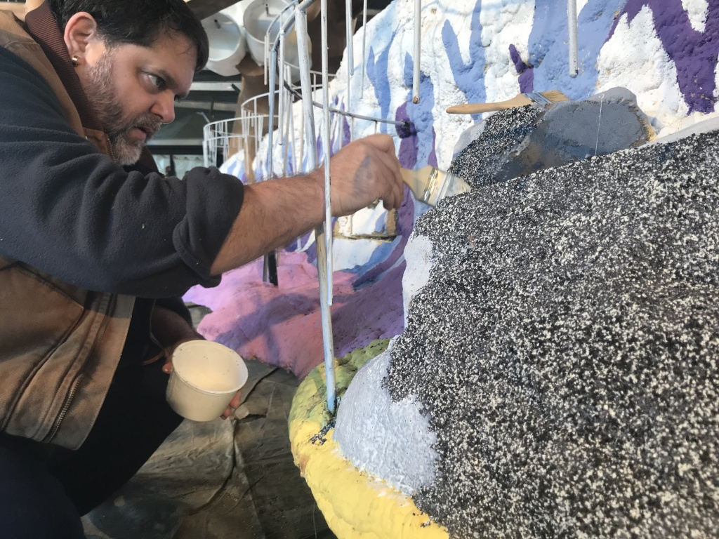 Volunteer Larry Geisz decorates part of the float with black and grey seeds
