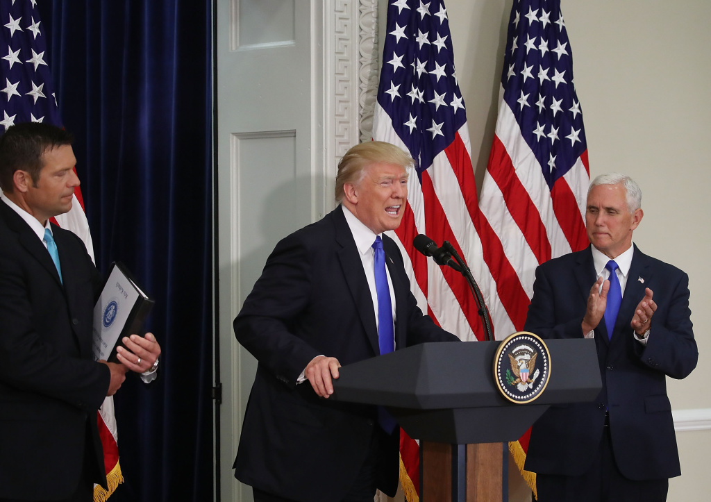 WASHINGTON, DC - JULY 19: U.S. President Donald Trump (C) speaks while flanked by Kansas Secretary of State, Kris Kobach (L) and US Vice President Mike Pence during the first meeting of the Presidential Advisory Commission on Election Integrity in the Eisenhower Executive Office Building, on July 19, 2017 in Washington, DC.  (Photo by Mark Wilson/Getty Images)