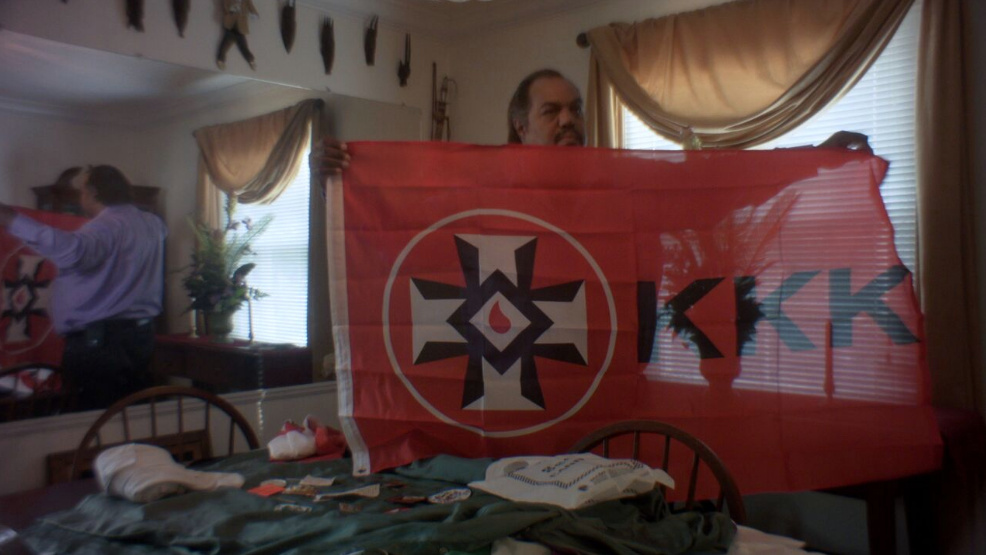 Daryl Davis displays KKK flag.