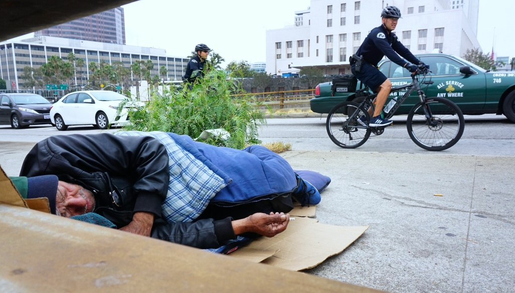 Los Angeles Police Department officers patrol on bicycles past a homeless man napping with cigarette in hand at his encampment on a downtown sidewalk in Los Angeles, California on June 7, 2017, a city facing a growing homeless population and less affordable housing.
