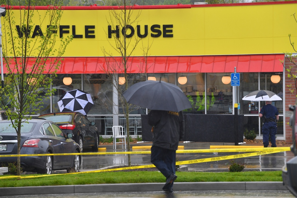 Law enforcement officers stand outside a Waffle House in Nashville, Tennessee where four people were killed and two were wounded after a gunman opened fire with an assault weapon on April 22, 2018.