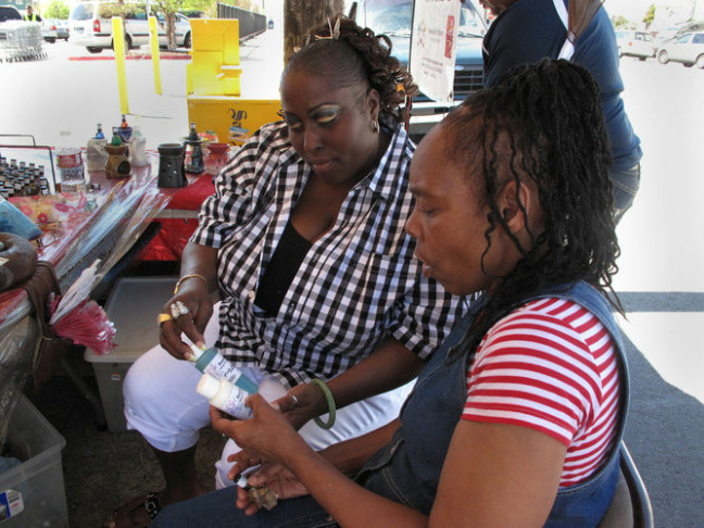 Yovanda Dixon (left) shows fellow group member Pamela Travis some of the bath oils she sells outside a San Francisco grocery store as part of her business Scentuality