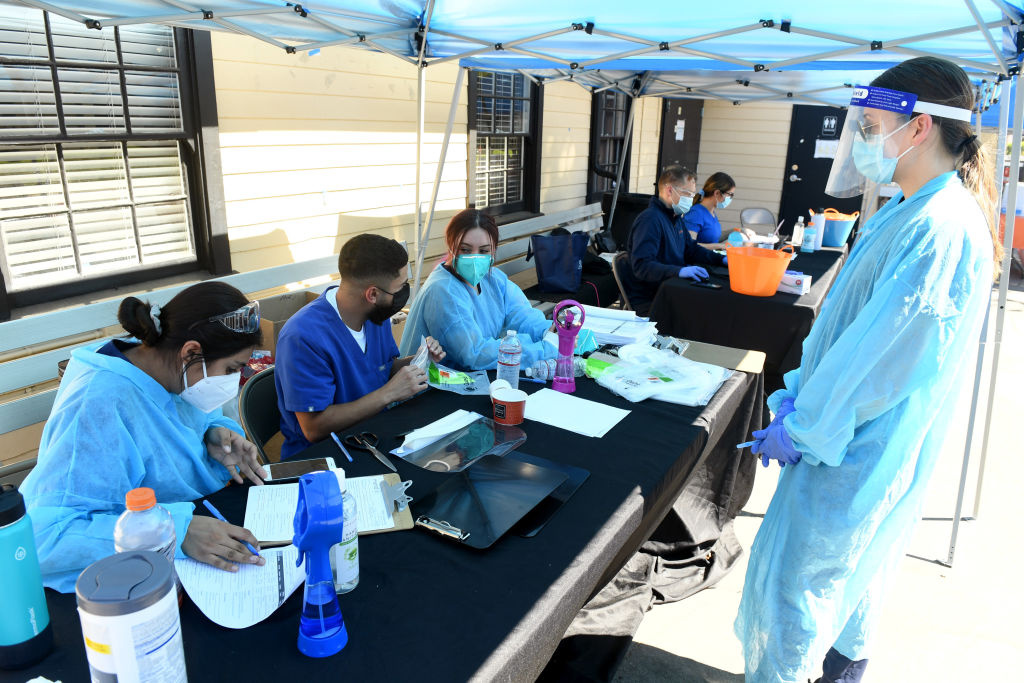 Mend Urgent Care workers wearing personal protective equipment perform drive-up COVID-19 testing at James Jordan Middle School on August 10, 2020 in Winnetka, California.