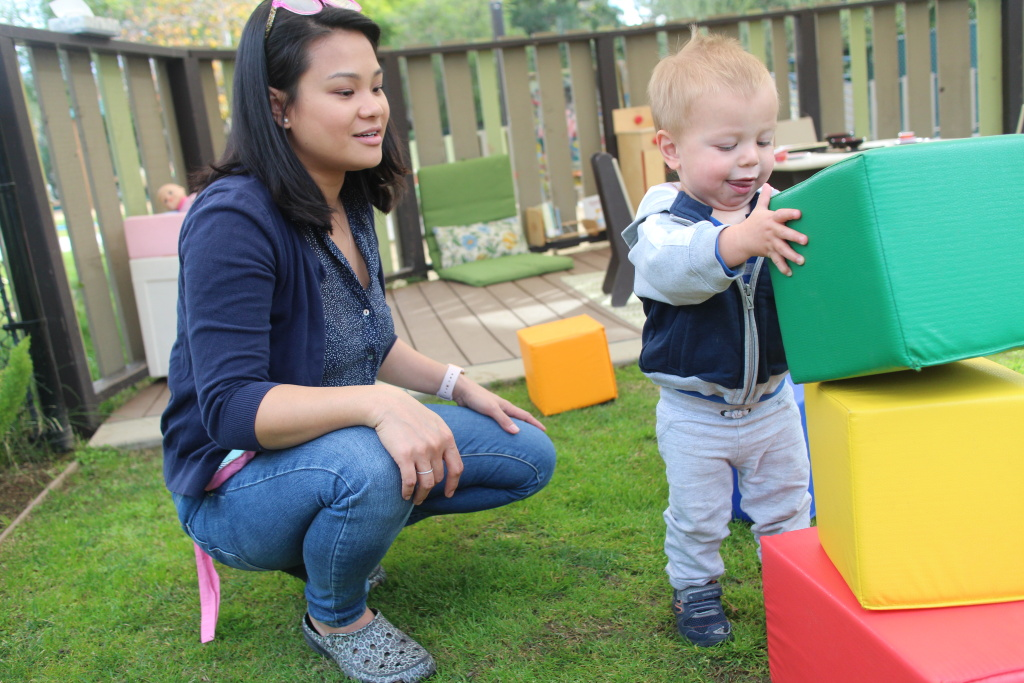 Eloisa McGah, lead teacher in the infant classroom at the Children's Center at CalTech, observes 18-month-old Elliot as he stacks blocks.