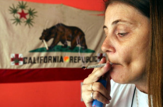 Staarla Heaney smokes a marijuana cigarette in front of the California state flag at the San Francisco Patients Cooperative, a medical cannabis cooperative, July 25, 2002 in San Francisco, California. A San Francisco city supervisor has drafted a proposal allowing voters in San Francisco to decide whether the city should consider getting into the marijuana growing business. Supervisor Mark Leno said he drafted the proposal because the Drug Enforcement Administration remains determined to close down clubs that distribute medical marijuana in San Francisco and other parts of California.
