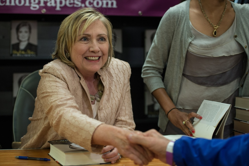 Former US Secretary of State Hillary Clinton shakes hands with an attendee as she signs her book 'Hards Choices' at the Bunch of Grapes bookstore on Martha's Vineyard on August 13, 2014. Clinton on August 12 denied attacking US President Barack Obama over his foreign policy in Syria and Iraq, insisting she was looking forward to 'hugging it out' with the US leader when they meet at a party later this week.