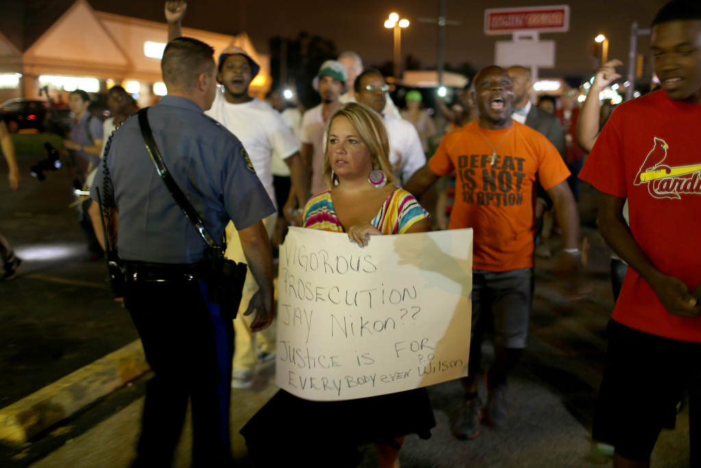 Police officers escort a protester carrying a sign that reads,
