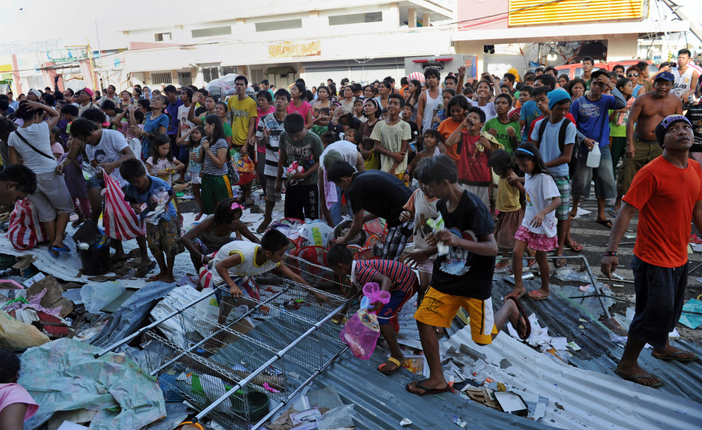 Residents (behind) watch as others (front) grab looted goods thrown out from the second floor of a warehouse in the town of Guiuan, Eastern Samar province in the central Philippines on November 11, 2013, only days after Super Typhoon Haiyan devastated the town on November 8. Philippines rescue workers struggled to bring aid to famished and destitute survivors on November 11 after the super typhoon that may have killed more than 10,000 people, in what is feared to be the country's worst natural disaster.