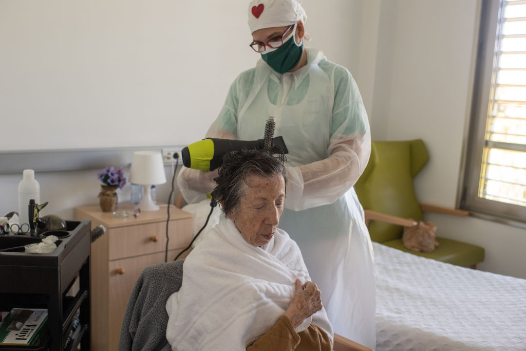 Rosa, hairdresser of La Mallola nursing home styles Carme Peris' hair before a visit of her close relatives on May 19, 2020 in Esplugues del Llobregat, near Barcelona, Spain.