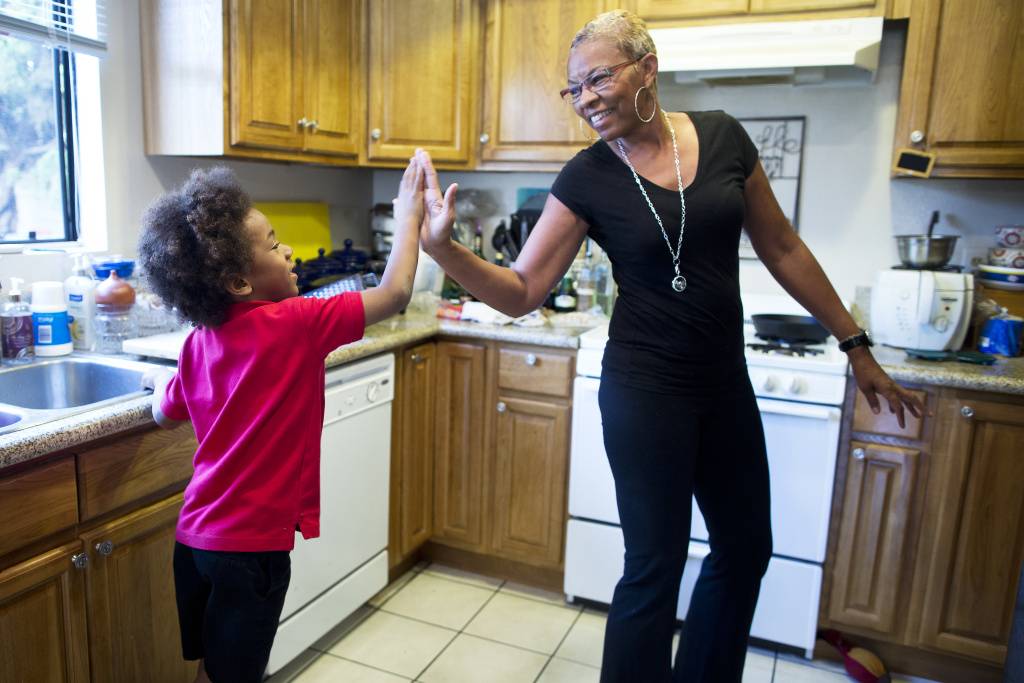 Tonia McMillian, a home-based child care provider, high-fives 6-year-old Skylar on Feb. 12 in her Bellflower home. In addition to her home care, McMillian also visits other childcare through the day as a consultant.