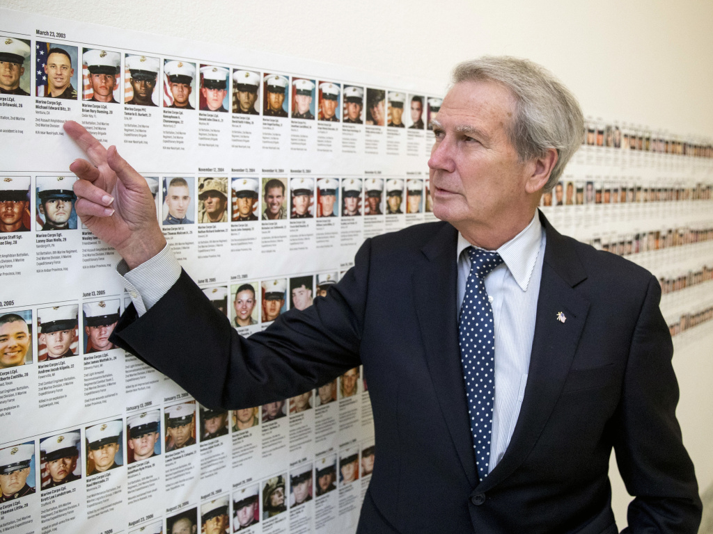 In this file photo, U.S. Rep. Walter Jones, R-N.C., stands in front of photos of fallen soldiers, along a hallway leading to his office on Capitol Hill in Washington. Jones, a once-fervent supporter of the 2003 invasion of Iraq who later became an equally outspoken Republican critic of the war, died Sunday.