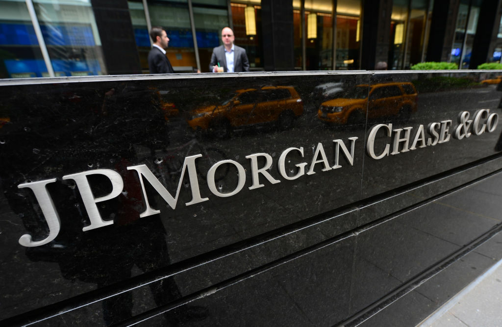 Two men speak outside JP Morgan Chase & Co headquarters in New York, May 14, 2012. A subsidiary of the company allegedly figured out a way to exploit vulnerabilities in California's electricity trading market during 2010 and 2011.