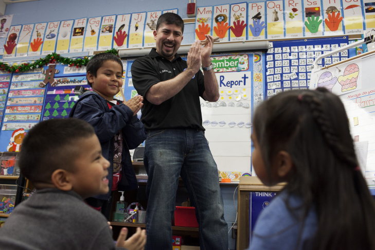 Hugo Villavicencio talks to kindergarten students in Maria Viera's class at Lenicia B. Weemes Elementary School about the importance of attending school. Villavicencio creates incentives for students to come to school, reinforcing positive associations with their education, he said.