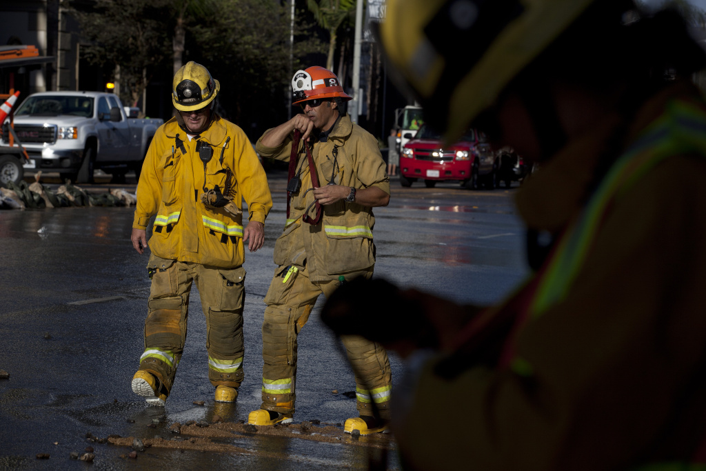 Los Angeles County Firefighters work to mitigate flooding on Sunset Boulevard after a water main break.