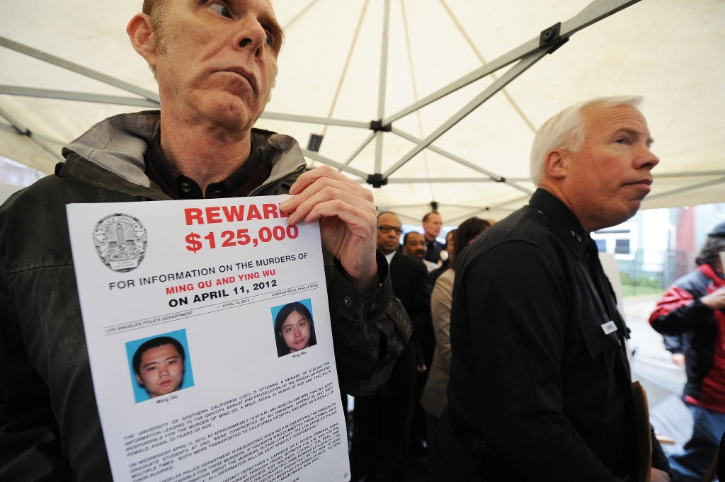 Los Angeles Police Department spokesman Richard French holds a poster offering a USD $125,000 reward for information leading to an arrest in the murder of Ming Qu (L) and Ying Wu (R), two University of Southern California (USC) students from China, during a news conference April 13, 2012 in the Los Angeles street where the murders occured two days ago.