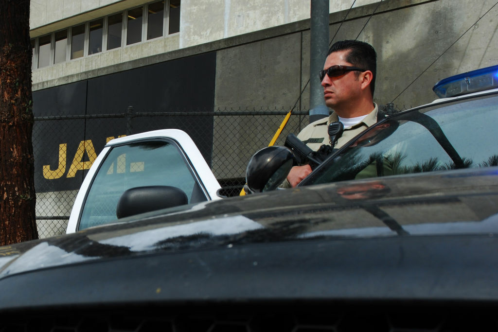 Sheriff's Deputy Rodriguez, an officer from the Los Angeles County Sheriff's Department, guards an intersection outside the Twin Towers Correctional Facility in Los Angeles on Feb. 8, 2013.