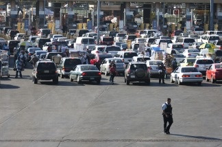 A member of the US Border Patrol walks behind the line of cars waiting to enter the United States from Mexico at the San Ysidro Port of Entry.