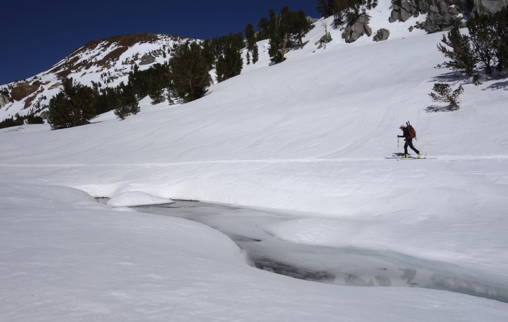 In this photo taken April 1, 2017, snow surveyor Kevin Klinefelter skis near a snow-covered stream near Bishop Pass in the Inyo National Forest near Bishop, Calif.