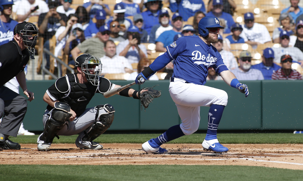 Max Muncy #13 of the Los Angeles Dodgers hits a ground ball during the first inning of a Cactus League spring training game against the Chicago White Sox at Camelback Ranch on February 24, 2020 in Glendale, Arizona.