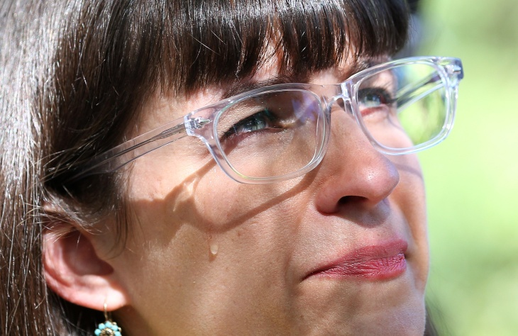In this Sunday, June 22, 2014 photo, a tear rolls down the face of Kate Kelly, the founder of Ordain Women, a prominent Mormon women's group, during a vigil in Salt Lake City. Kelly found out Monday that she had been excommunicated from the church.
