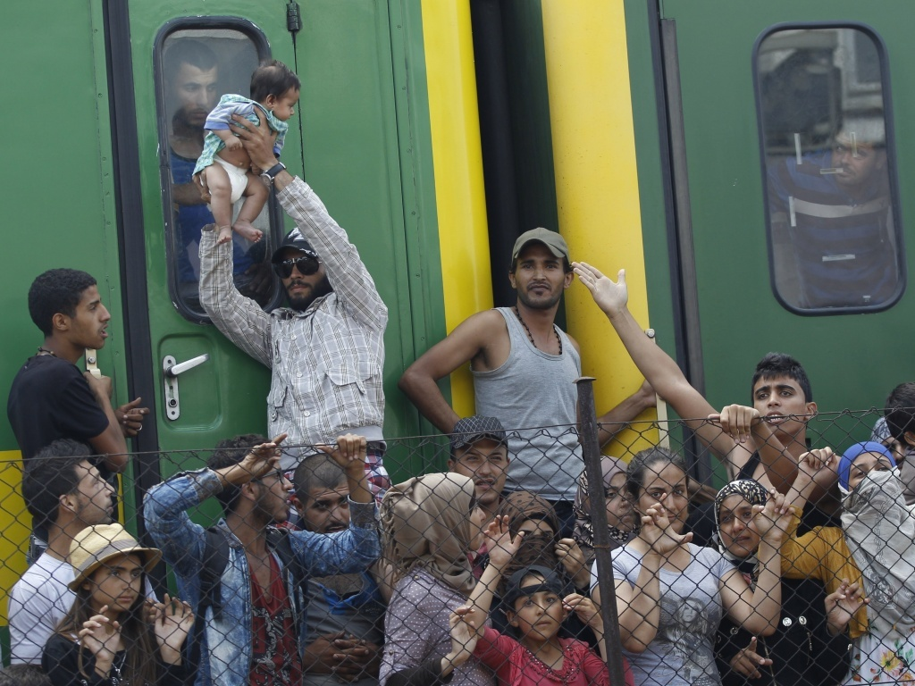 A man lifts up a child next to a train that was stopped in Bicske, Hungary, on Friday. More than 150,000 people have reached Hungary this year, most coming through the southern border with Serbia.
