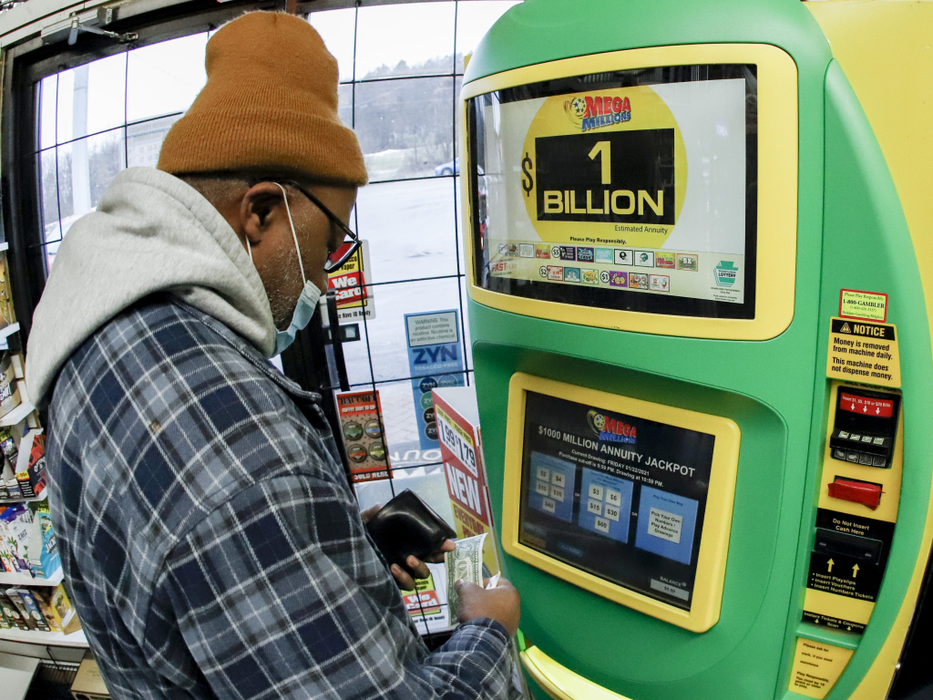 A patron, who did not want to give his name, uses the lottery ticket vending kiosk at a Smoker Friendly store to purchase tickets for the Mega Millions lottery drawing in Cranberry Township, Penn. The jackpot for the Mega Millions lottery game grew to $1 billion ahead of Friday night's drawing after months without a winner.