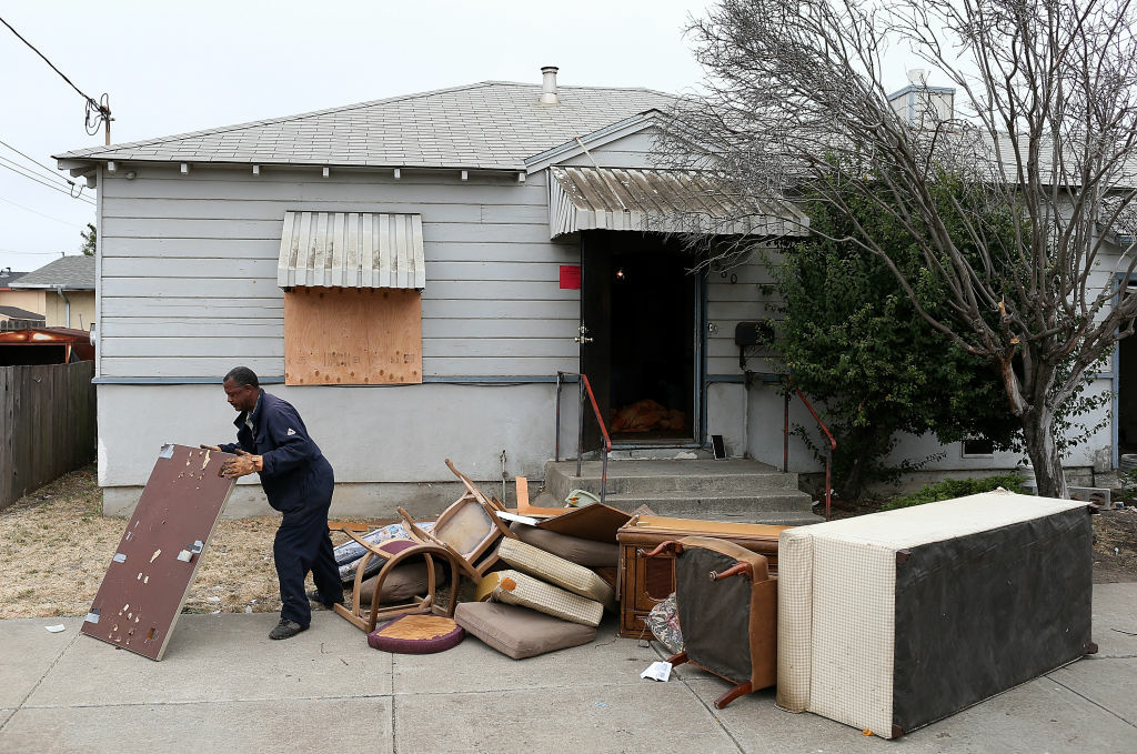 A worker removes furniture from a foreclosed home before the start of a bus tour of foreclosed and blighted properties on July 13, 2012 in Richmond, California.  Members of the group Alliance of Californians for Community Empowerment (ACCE) joined city officials and Richmond mayor Gayle McLaughlin on a bus tour to view foreclosed properties in neighborhoods in Richmond that have been hit the hardest by foreclosures. Richmond currently has over 1,000 homes in foreclosure.
