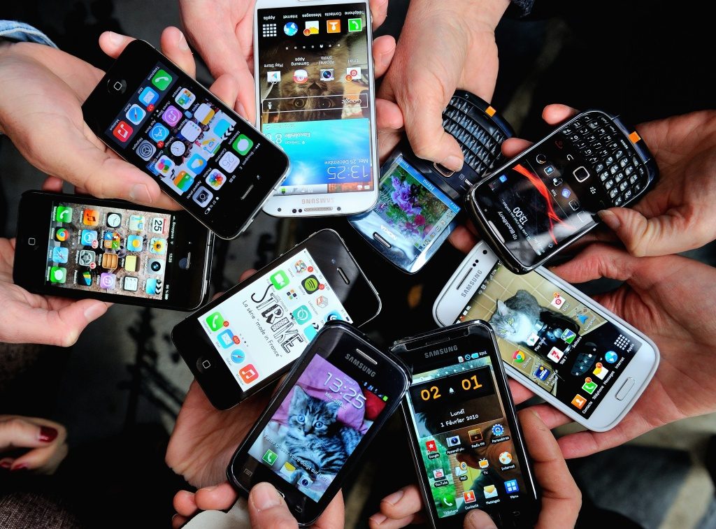People show their smartphones on December 25, 2013.