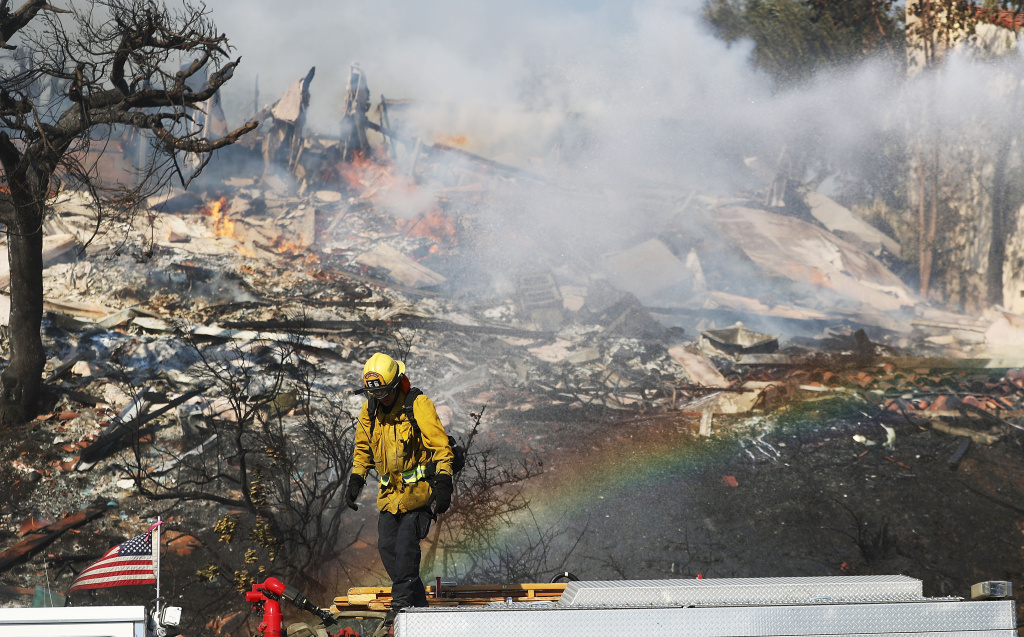 VENTURA, CA - DECEMBER 05: A firefighter works while battling flames from the Thomas Fire in a residential neighborhood on December 5, 2017 in Ventura, California. Around 45,000 acres have burned with 150 structures destroyed in the fire, forcing thousands to evacuate. (Photo by Mario Tama/Getty Images)