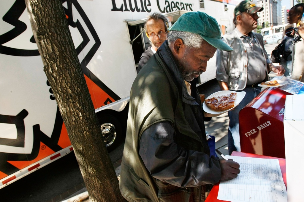 Former Army Sgt. Dennis Anderson, a homeless veteran, signs up as he  gets a slice of pizza that was handed out from the Little Caesars Love Kitchen, a mobile pizza kitchen, in front of the Department of Veterans Affairs building September 17, 2007 in Washington, DC. The Love Kitchen was in town to provide hot pizza meals to homeless people including homeless veterans. Little Caesar's founder Michael Ilitch was awarded with the Secretary's Award Monday by the Department of Veterans Affairs to recognize his support of veterans.