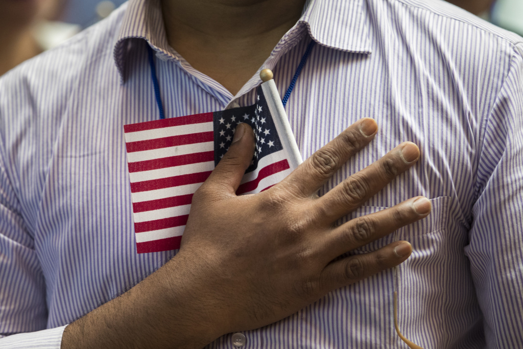 A new U.S. citizen holds a flag to his chest during the Pledge of Allegiance during a naturalization ceremony at the New York Public Library, July 3, 2018 in New York City.