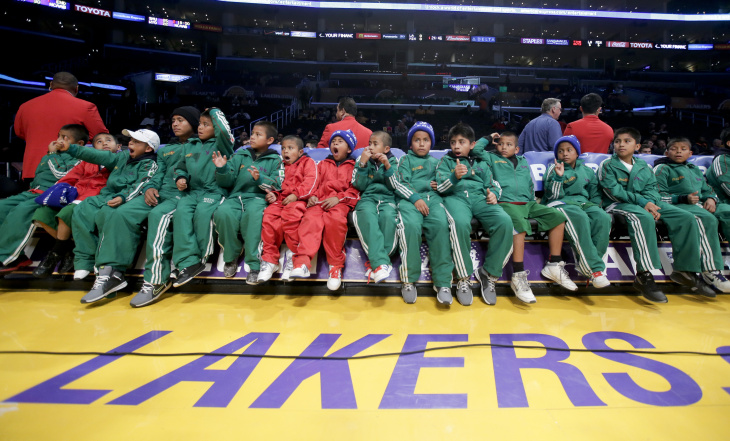 Members of the Triqui kids basketball team, made up of children from the mountainous region of the Mexican state of Oaxaca sit on the Los Angeles Lakers bench before an NBA basketball game against the Minnesota Timberwolves in Los Angeles, Friday, Dec. 20, 2013.