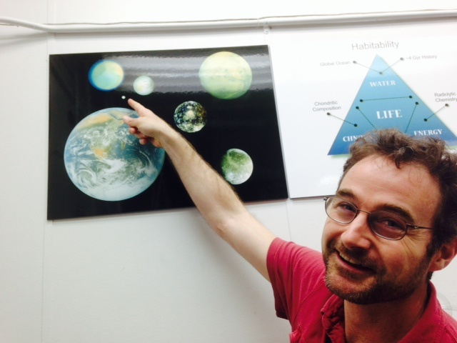 Kevin Hand shows off a poster with Earth and all the other planets and moons scientists life may exist. Hand points to Saturn's moon Enceladus which is smaller than Earth's moon.