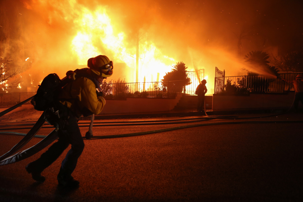 PORTER RANCH, CALIFORNIA - OCTOBER 11: Firefighters work on a house fire during the Saddleridge Fire in the early morning hours on October 11, 2019 in Porter Ranch, California. The fast moving wind-driven fire has burned more than 7,500 acres and destroyed 25 structures. (Photo by Mario Tama/Getty Images)