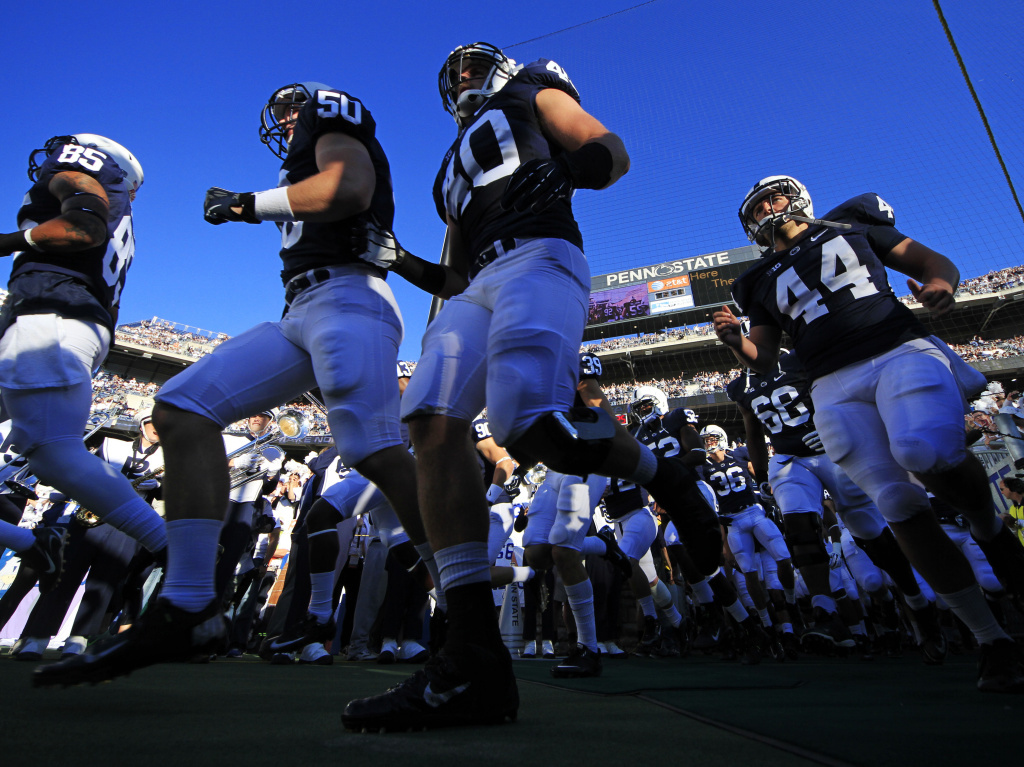 Penn State football players run on to the field earlier this month in State College, Pa.