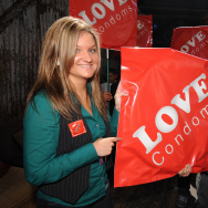 AIDS activists carry large condom packet