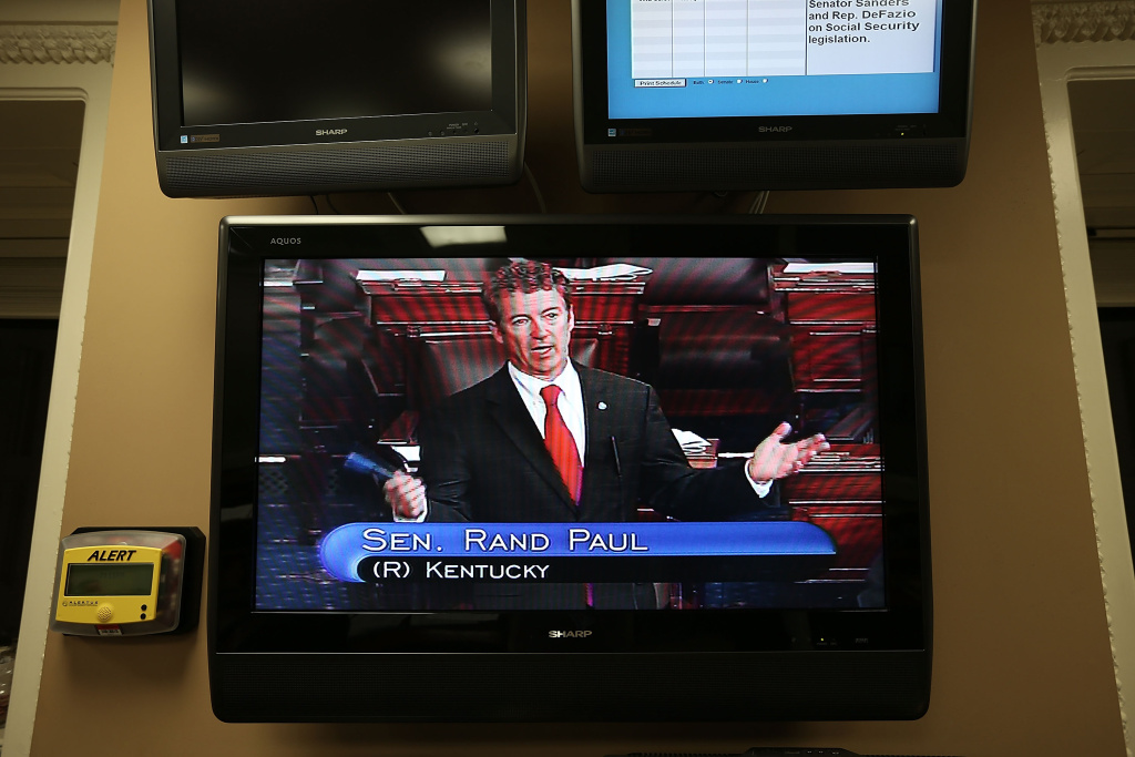 U.S. Sen. Rand Paul (R-KY) is seen on a TV monitor as he participates in a filibuster on the Senate floor March 6, 2013 on Capitol Hill in Washington, DC. Along with opposing the nomination of John Brennan to be the next director of CIA, Paul spoke at length about drones.