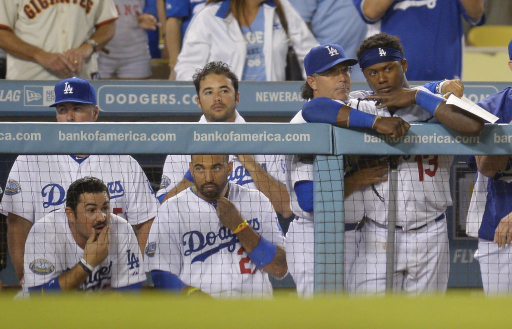 Members of the Dodgers watch from the dugout during the ninth inning of their baseball game against the San Francisco Giants, who won 4-3. With that loss, the Dodgers were eliminated from playoff contention.