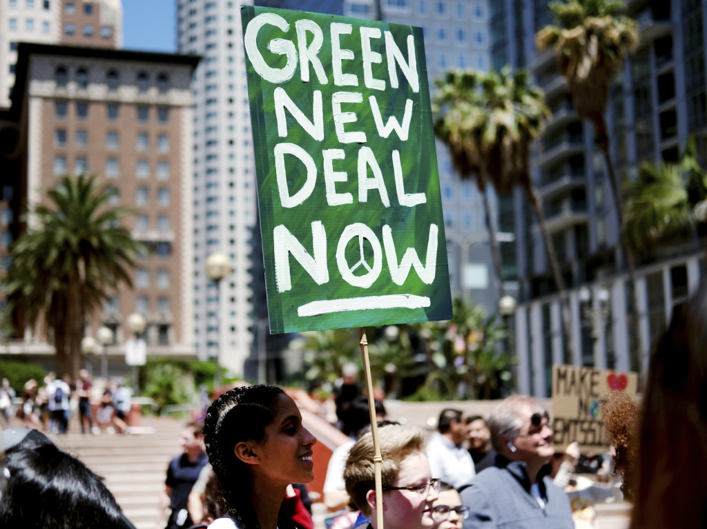 Climate change activists holding signs join in on a rally supporting the