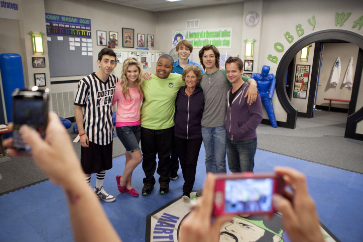 Studio teacher Linda Stone works with teen actor Leo Howard at his desk on set for the Disney XD show