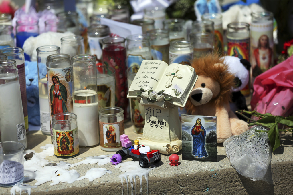 A sidewalk memorial dedicated to the teacher and student who were shot to death Monday at North Park Elementary School in San Bernardino, Calif., is displayed Tuesday, April 11, 2017. Jonathan Martinez, a special needs student of teacher Karen Smith, died when Smith's estranged husband shot both in her classroom. (AP Photo/Reed Saxon)