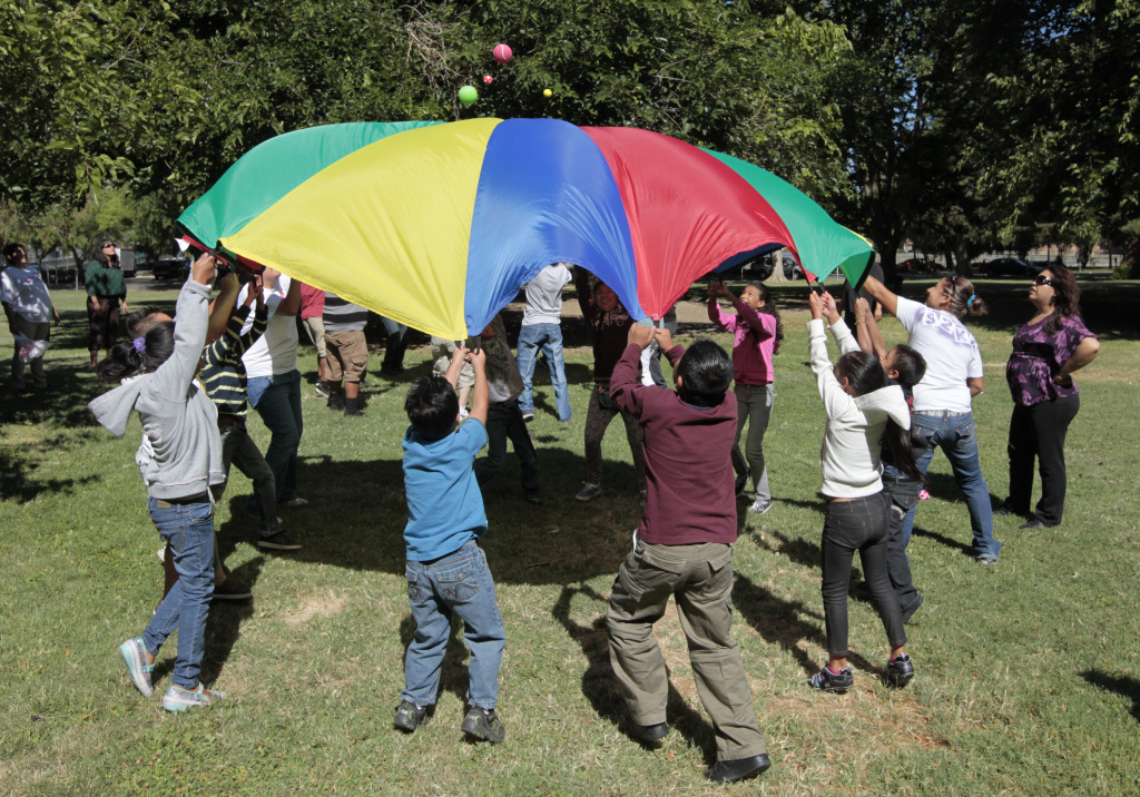 In this July 26, 2012, photo children and adults uses a play parachute as part of an exercise activity during a wellness program run jointly by the La Familia Counseling Center and the YMCA in Sacramento. Voters approved Proposition 63 in 2004 to provide funding for mental health services, but a California watchdog agency, the Little Hoover Commission, reported Thursday, Sept. 8, 2016, that 12 years after voters approved a 1 percent tax on millionaires, the state still can't readily show how the money is spent or who is helped.