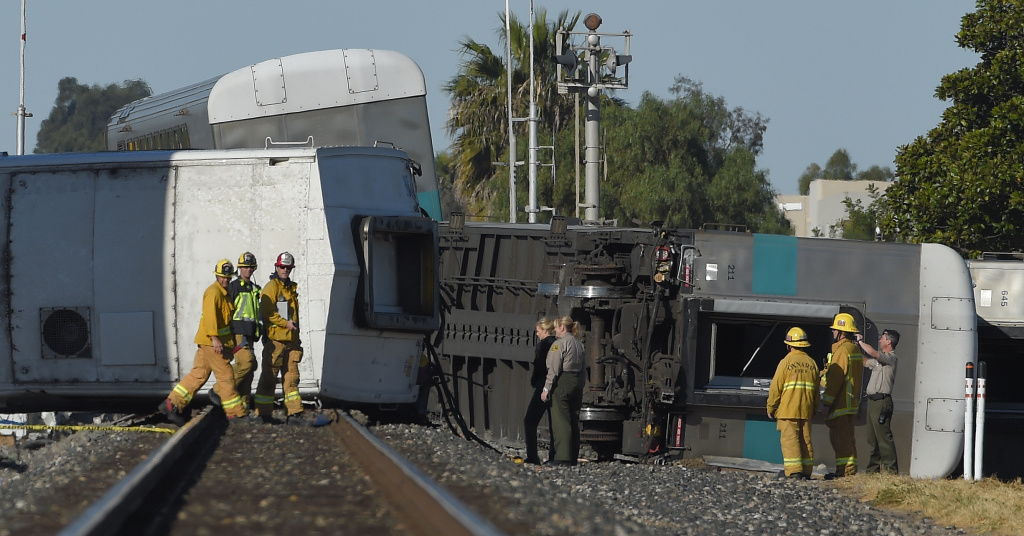 Firefighters and other officials walk near cars from a Metrolink passenger train that derailed Tuesday, Feb. 24, 2015, in Oxnard, Calif. Three cars of the Metrolink train tumbled onto their sides, injuring dozens of people in the town 65 miles northwest of Los Angeles. Metrolink spokesman Scott Johnson told the Los Angeles Times that at least 30 people were injured.