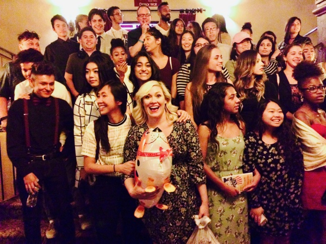 Second City cast members Carisa Barreca (front center) and Tien Tran (center left) strike a pose with student fans in the Fox Theater lobby.