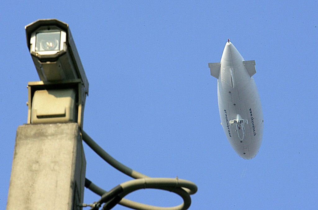 A hi-tech zeppelin is seen during a flight next to a traffic control camera in central Athens 25 July 2004.