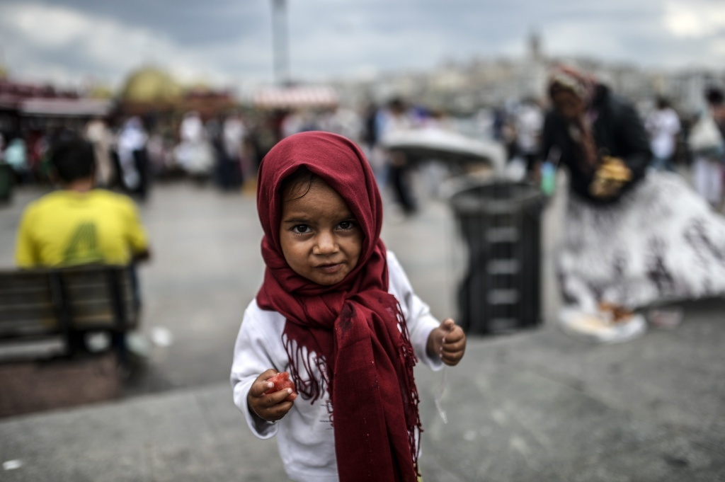 A Syrian refugee child eats food which her mother collected from rubbish in the Eminonu disctrict of Istanbul.
