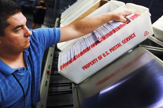 Julio Galligaris sorts through mail-in ballots that have been cast and received at the Miami-Dade Election Department headquarters on Oct. 13 in Doral, Fla.