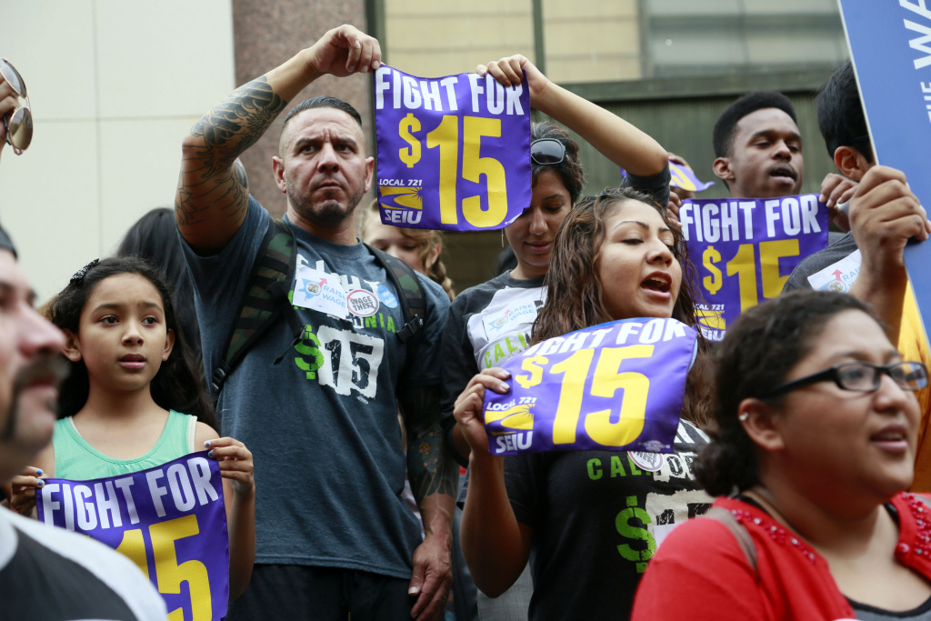 In this July 21, 2015 photo, workers hold a rally in Los Angeles in support of the Los Angeles County Board of Supervisors' proposed minimum wage ordinance. On March 26, California legislators and labor unions reached an agreement that will take the state's minimum wage from $10 to $15 an hour.